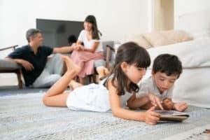 children playing tablet on carpet